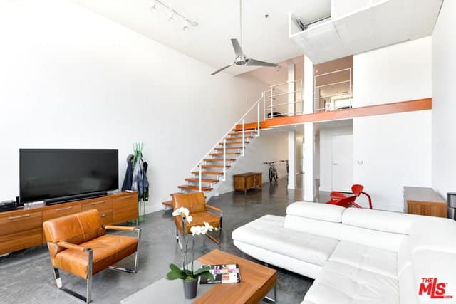 Industrial-style living room with exposed steel beams, polished concrete floors, and track lighting.