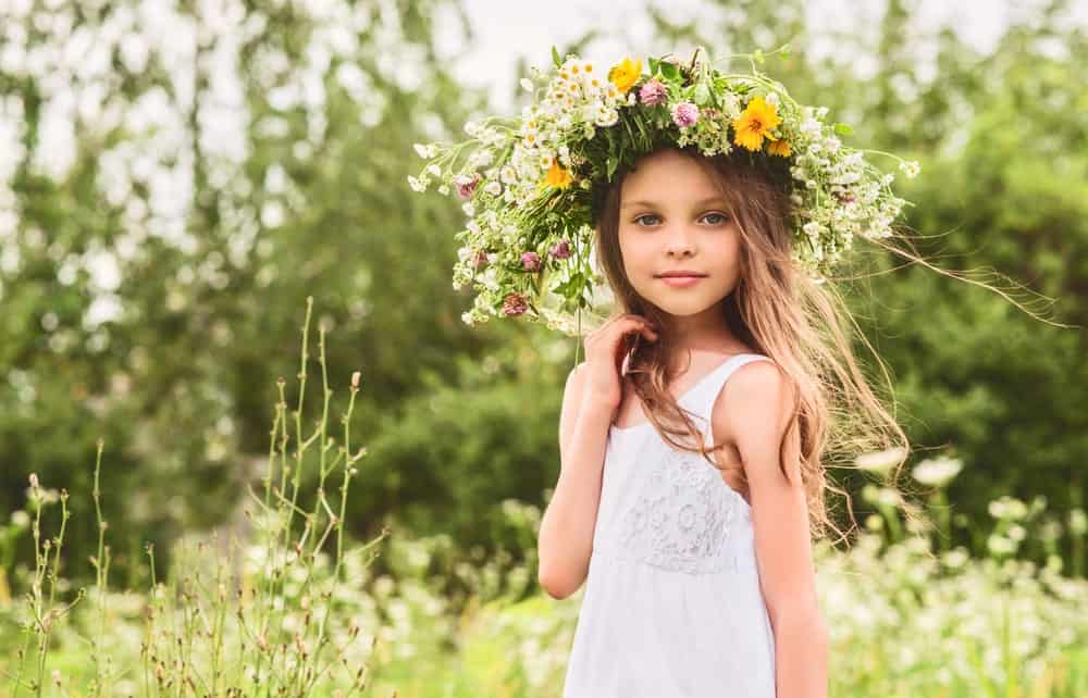 A Girl Flaunting a Flower Wreath Outdoors