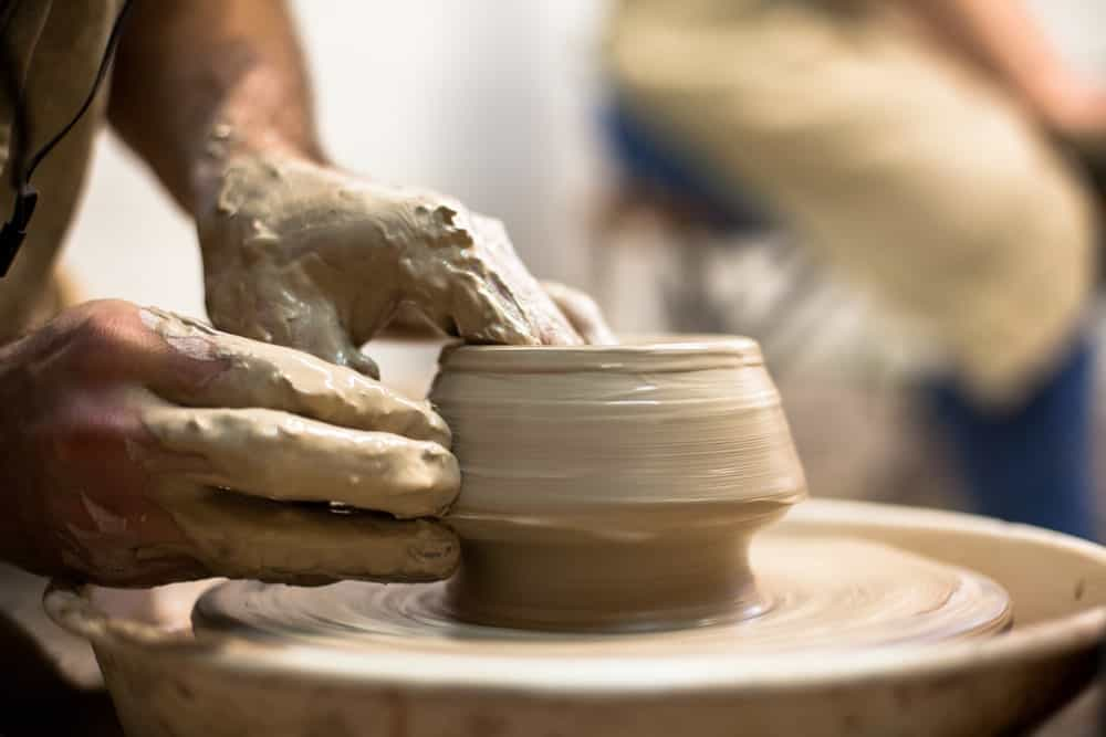 A potter working with clay to make a pot