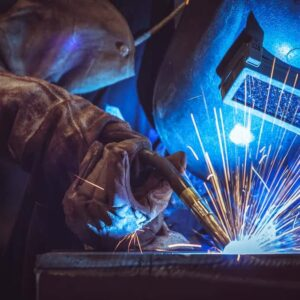 A welder in safety gear working at a factory