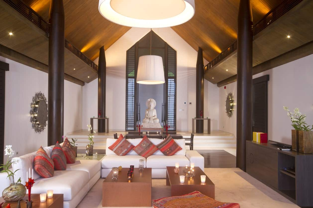 This large and airy living room has an aura of a temple with its high cathedral ceiling, large dark pillars and a large white marble Buddha statue at the far end of the hall-like living room that has white leather sofas and wooden coffee tables.
