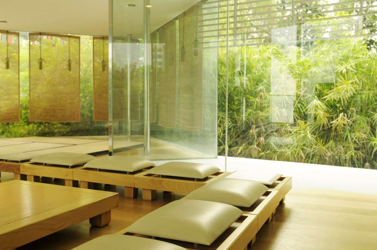 This Japanese-Style living room has comfortable cushioned wooden seats low on the light hardwood flooring surrounding a low wooden coffee or tea table in the middle. This is given a serene background of bamboo trees featured by glass walls.