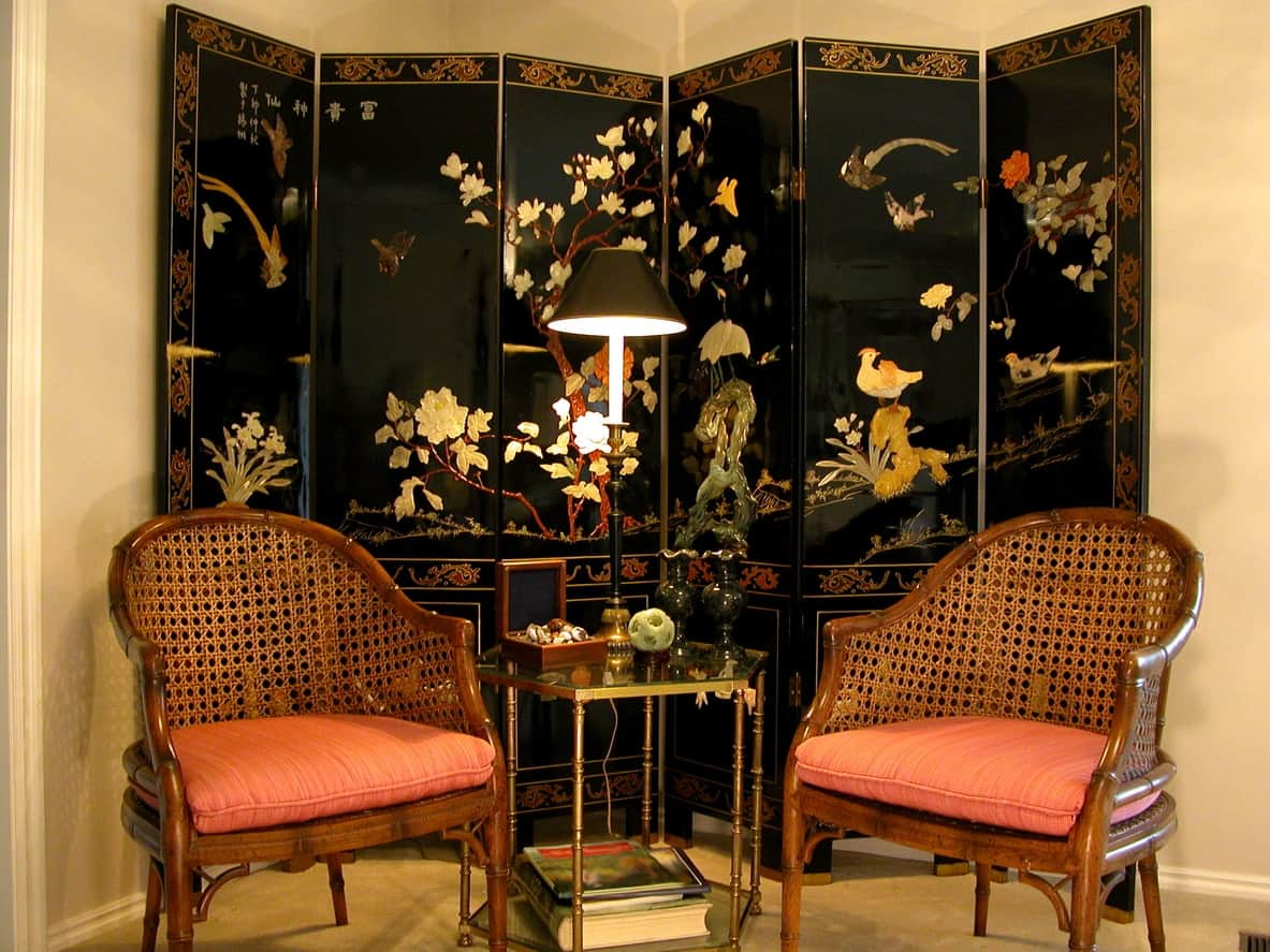 This small living room has two armchairs with woven wicker backs and orange-cushioned seats flanking a modern glass-top side table that stands out against the elegant black folding panel with classic oriental patterns.