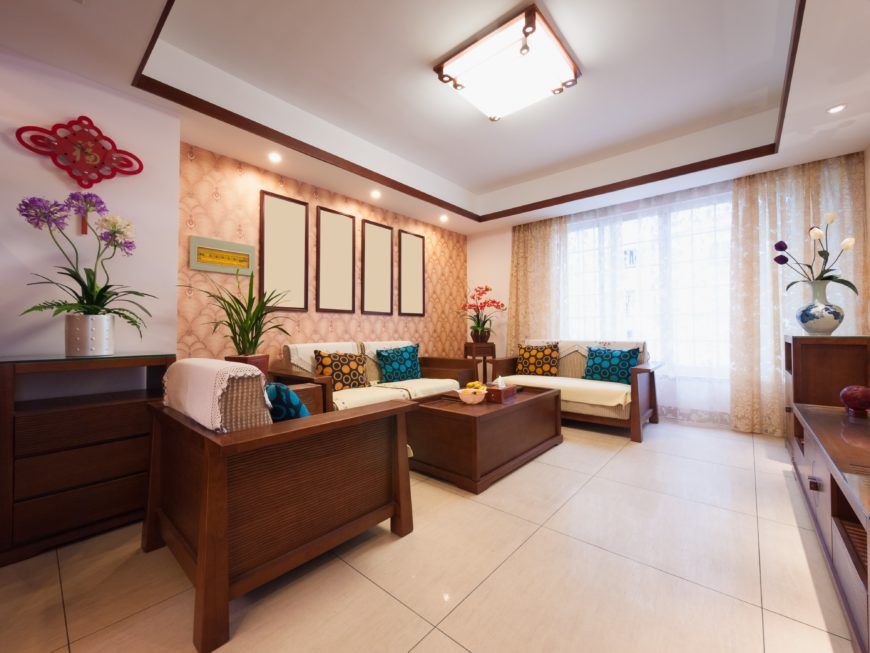 The white tray ceiling has a square flush light that illuminates the beige floor tiles and patterned wall augmented by the curtained tall windows behind the wooden benches that has white cushions and colorful patterned pillows.