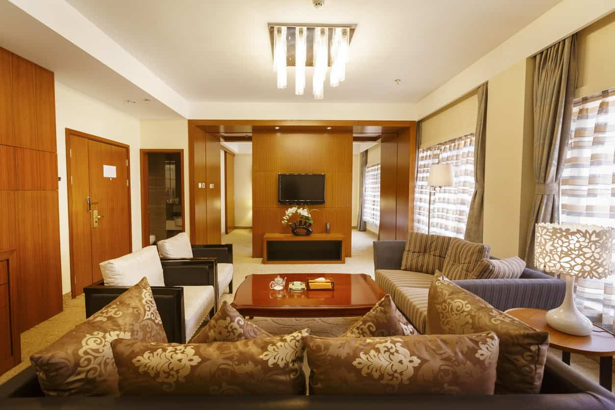 The dark cushioned sofa has oriental patterns on its brown pillows that matches with the patterns of the white table lamp on a round side table. The wooden coffee table matches with the wooden elements of the walls and door contrasting the white tray ceiling.