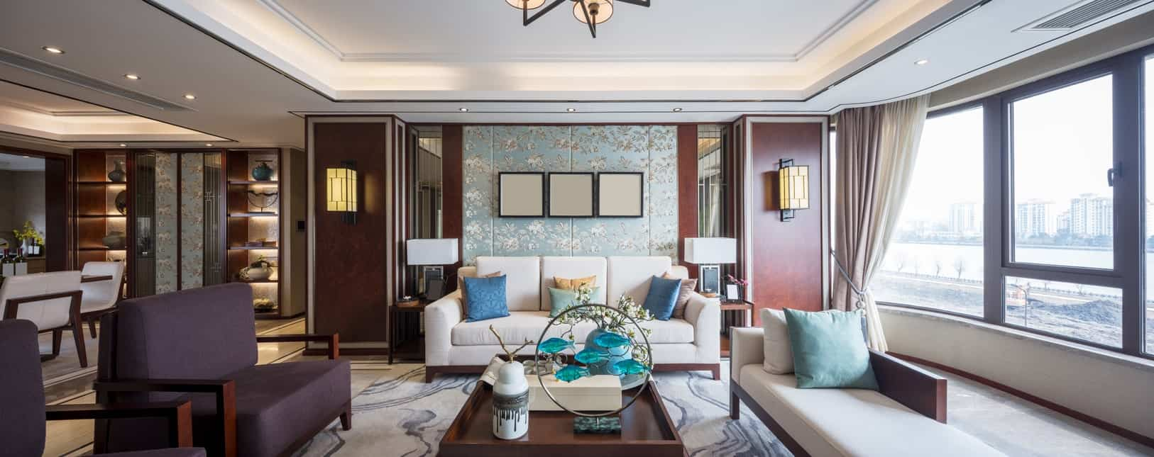 The wall behind the white cushioned sofa is dominated by decorative panels with light blue floral patterns that provide a nice contrast to the dark brown columns with wall-mounted oriental lanterns matching the chandelier of the white tray ceiling.