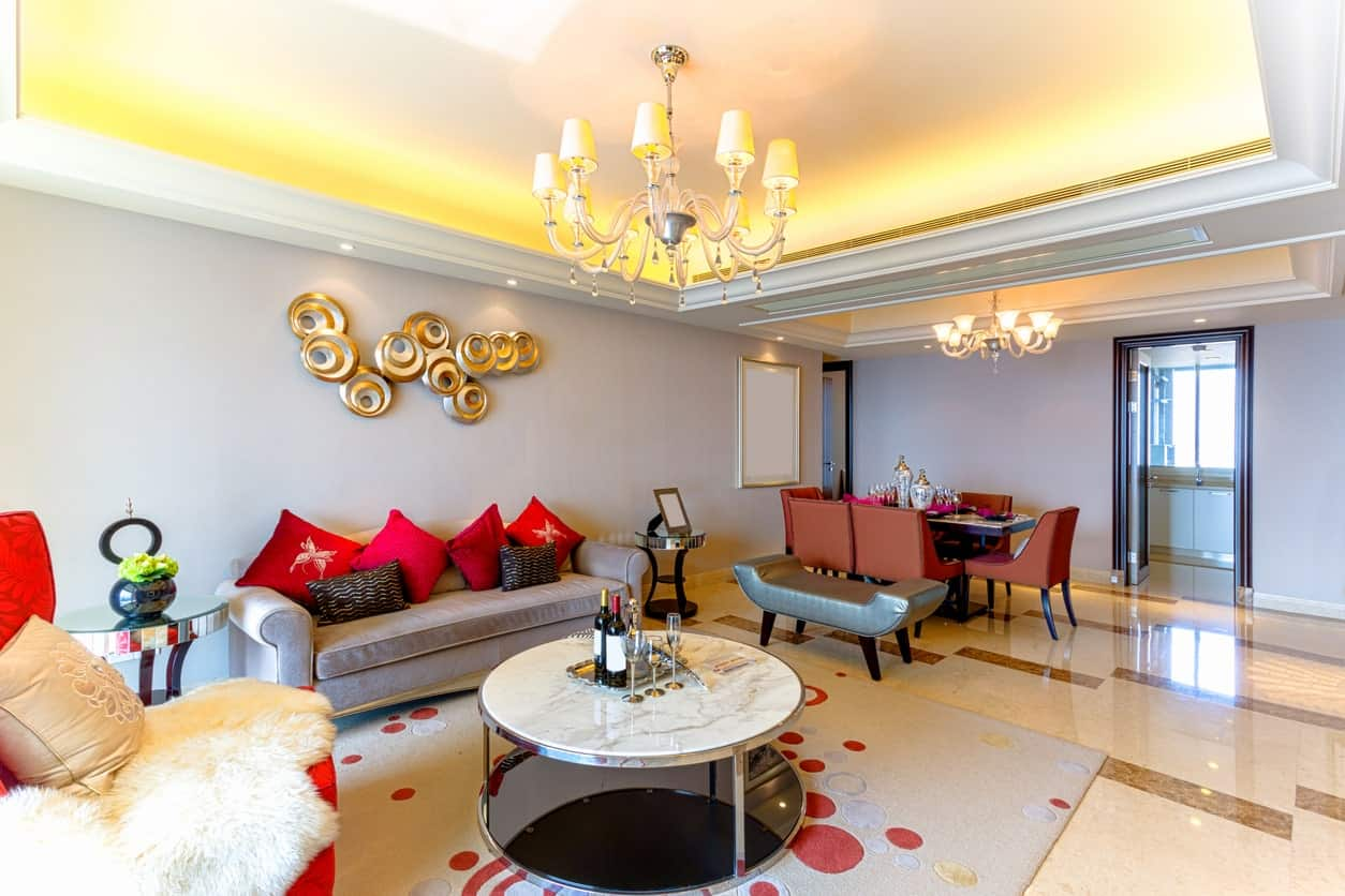 The light gray walls serve as a nice background for the elegant golden artwork over the gray velvet sofa. This decor is augmented by the brilliant chandelier of the yellow cove ceiling. The gray area rug under the white marble coffee table has red sports that match the pillows of the couch.