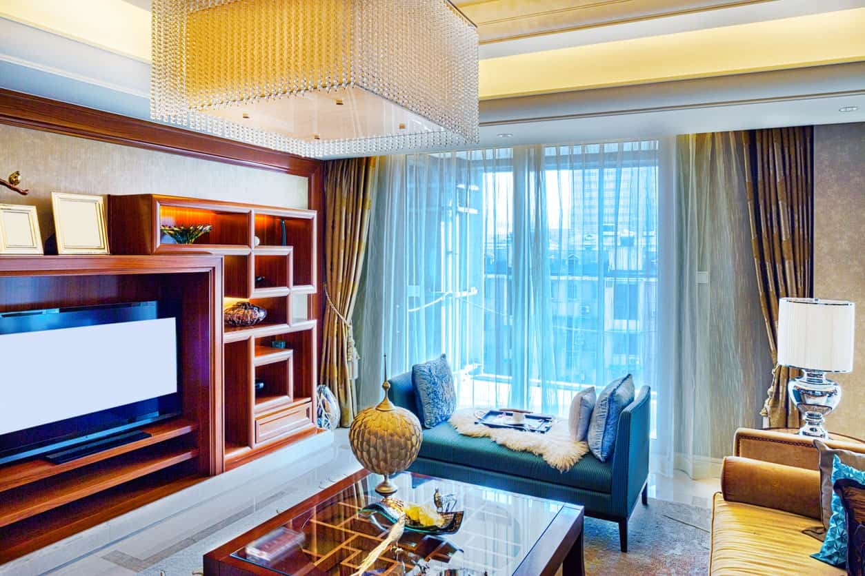 The brilliant crystal cube pendant light of the white tray ceiling is contrasted by the redwood elements of the glass-top coffee table and the wooden structure of the TV that has oriental-style shelves matching the wooden molding.