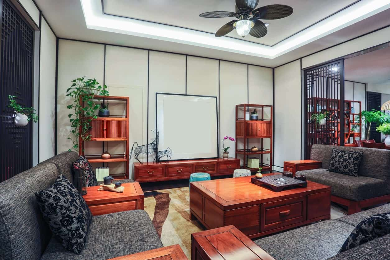The white tray ceiling has a ceiling-mounted fan on it that has a flower petal design fitting in with the floral patterns of the black pillows on the black cushioned benches. The stand-out elements here are the red wood elements of the large coffee table and benches.