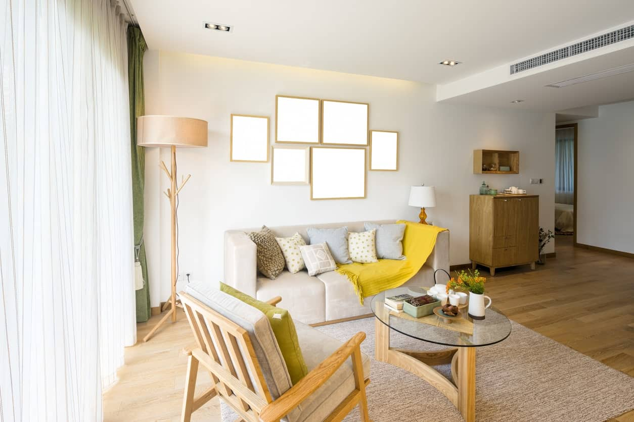 The white ceiling and walls are further brightened by the curtained windows that complements the light hardwood flooring. This matches with the wooden armchair, standing lamp as well as the frame of the glass-top elliptical coffee table.