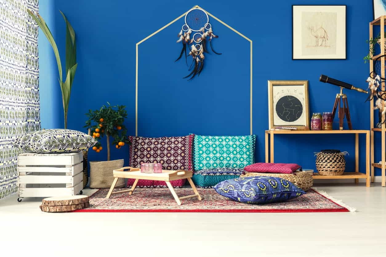 The bright patterned pillows and chair cushions are paired with a colorful area rug and a blue wall for that unique Arabian quality that is augmented by wooden elements as well as a framed artwork of a camel.