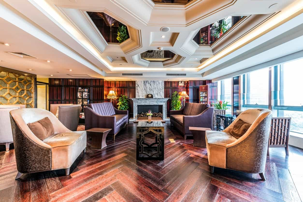 The herring bone patterns of the hardwood flooring is paired with oriental patterns on the coffee table and the brilliant coffered ceiling that has mirrors illuminated by the large glass windows and complemented by a white marble fireplace on the far end.