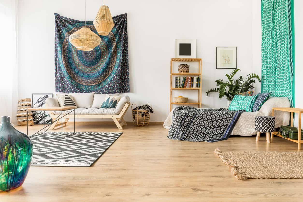 The colorful patterned fabrics and area rug are a nice contrast for the white walls and light hardwood flooring that matches with the pendant lights, wooden frame of the cushioned bench as well as the wood-topped modern coffee table.