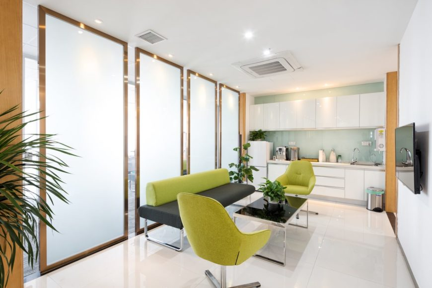 The large golden framed panels of frosted glass serve as a nice background for the modern sofa and pair of cushioned armchairs that have an avocado green hue contrasted by the white floor tiles and modern sleek black coffee table.