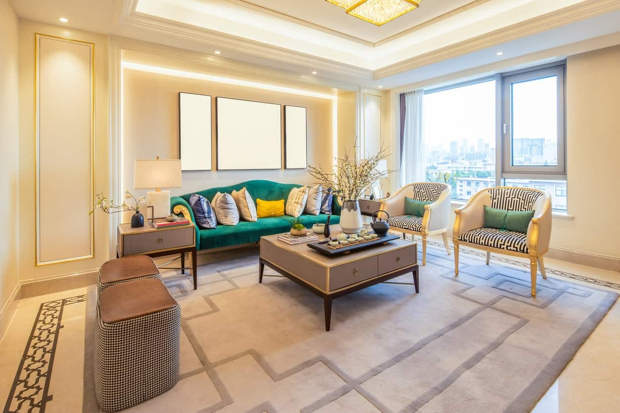 The beige marble flooring of this elegant living room is dominated by a gray area rug with oriental patterns that matches well with the cushions of the armchairs that stands out against the green sofa and its beige wall with edge lighting.