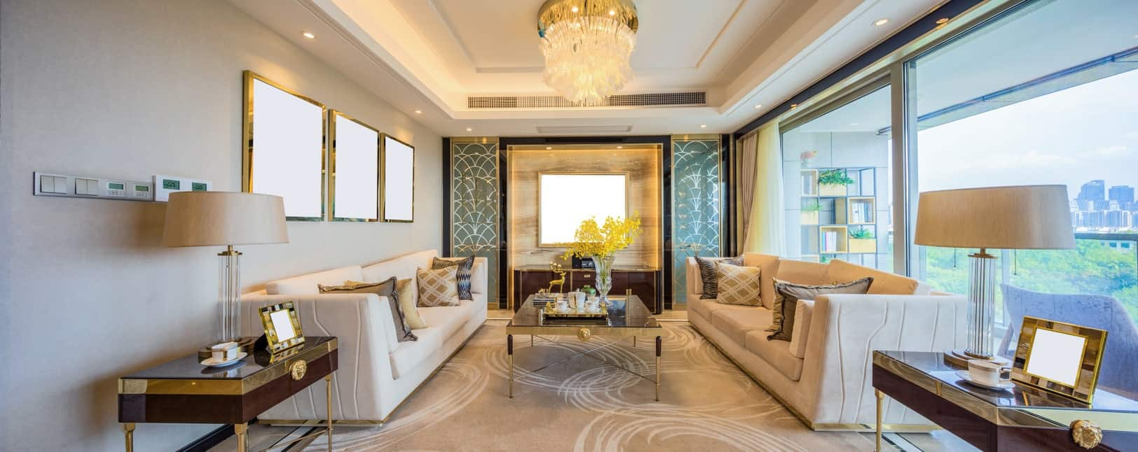 The white tray ceiling features a brilliant crystal flush mount lighting that raises the aura of elegance of the living room that has two beige cushioned sofas flanking a modern coffee table facing a wall flanked with oriental green panels.