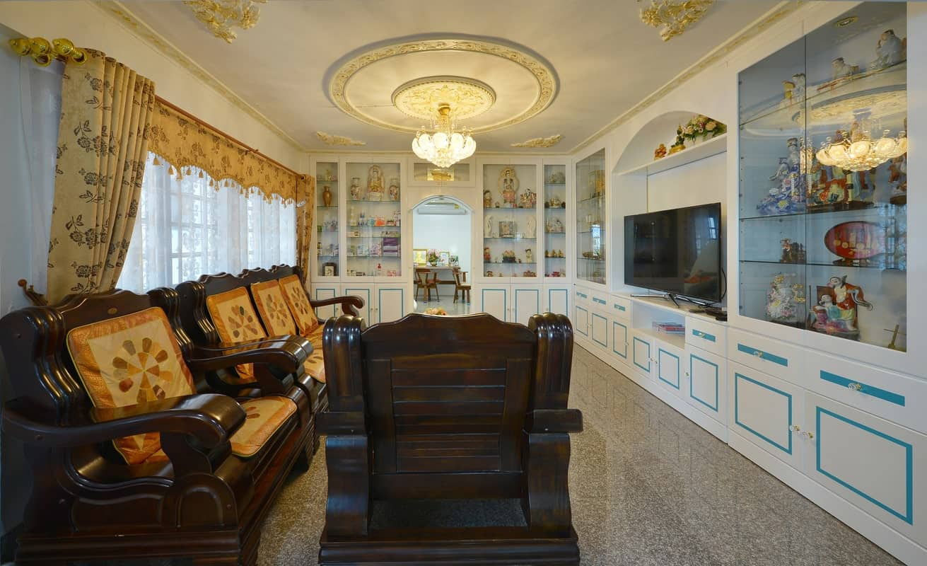 The matching dark wooden armchairs and benches of this simple living room is contrasted by the large white china cabinet the is dominating two adjacent walls. This china cabinet features multiple oriental decors in its glass cabinets.