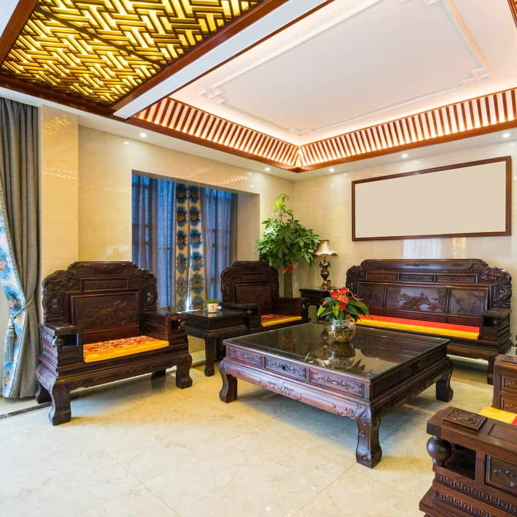 The brilliant white tray ceiling is adorned with oriental wooden patterns that play well with the carved designs of the wooden armchairs and bench surrounding the large wooden glass-top coffee table that stands out against the white marble flooring.