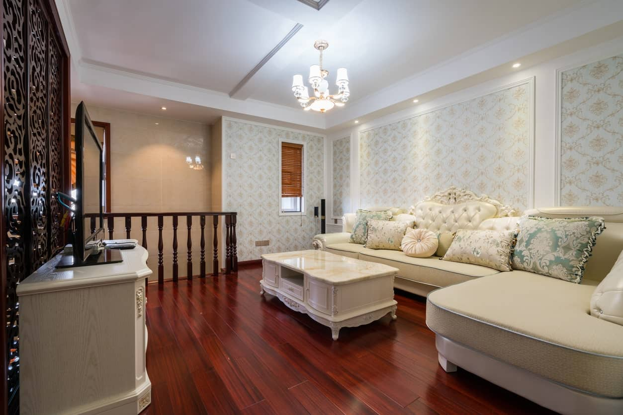 The sleek redwood flooring of this elegant living room is contrasted by the light hues of the white leather sectional sofa against the white walls that are dominated by beige patterns of the wallpaper as well as the white coffered ceiling.