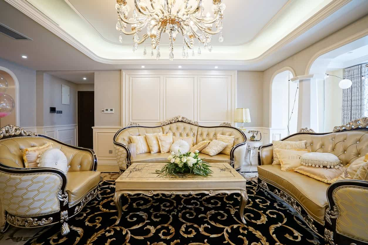 The patterns of the black area rug is complemented by the elegant designs of the beige leather sofas and their beige wooden coffee table illuminated by the brilliant crystal chandelier of the white tray ceiling.