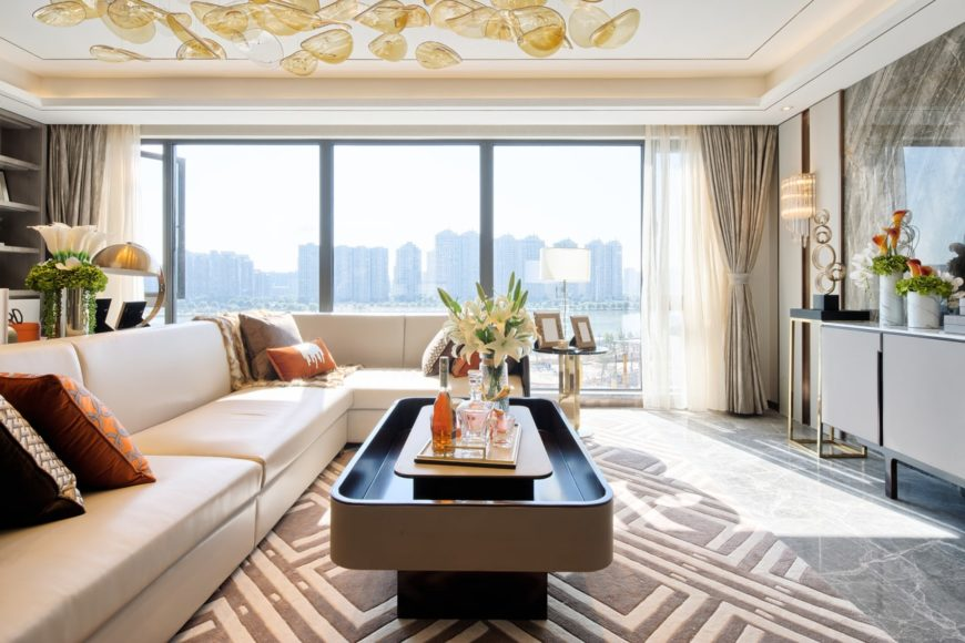 The white ceiling is adorned with yellowish glass that serves as an overhead decoration complementing the L-shaped white sectional sofa and its modern coffee table over the gray patterned area rug covering the marble flooring.