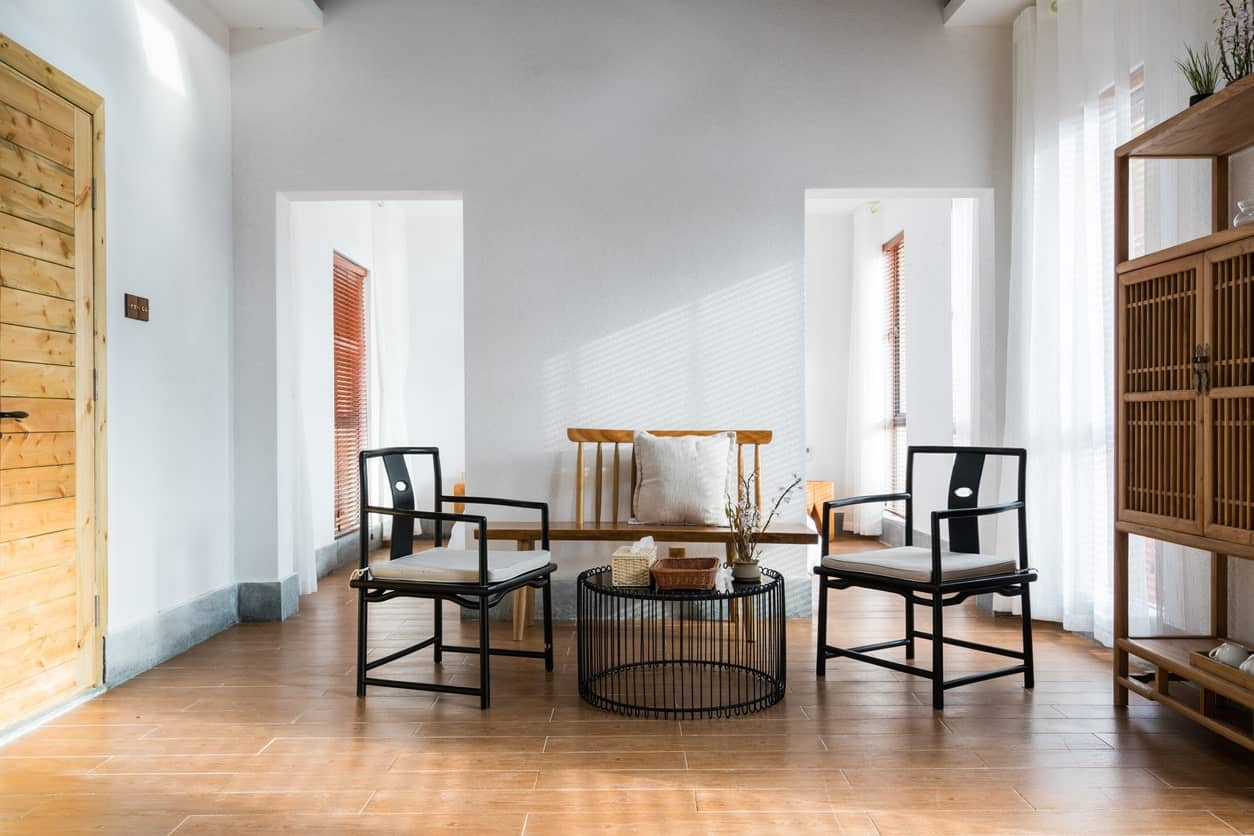 This simple living room has white walls and curtains windows that illuminate the light hardwood flooring that makes the black armchairs and modern coffee table stand out. This is paired with a wooden bench that matches the chinese cabinet on one side.