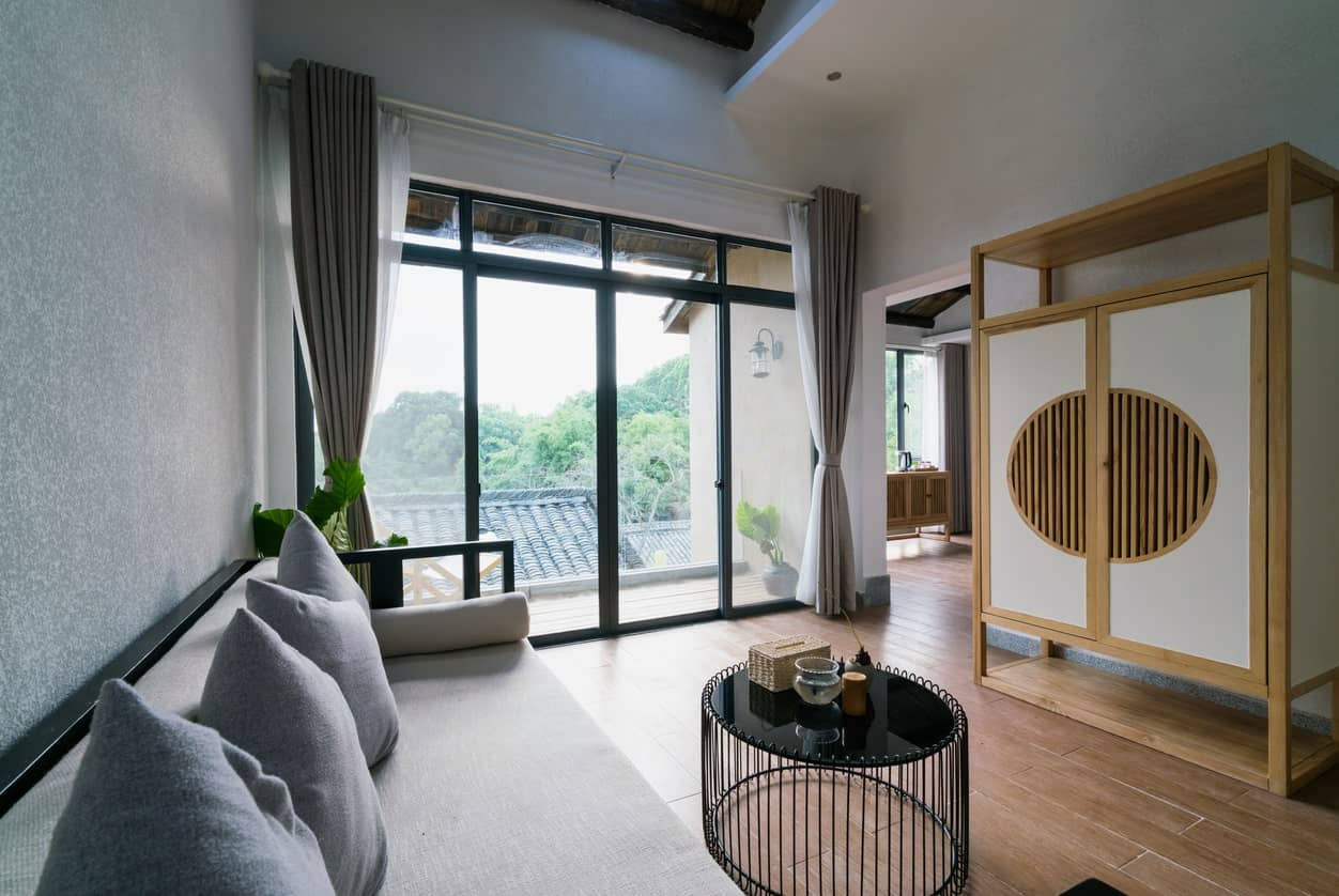 The white Chinese cabinet has wooden frames that complements the hardwood flooring that is lightened up by the sliding glass doors that shine natural lights on the gray walls and matching sofa with a modern black coffee table.