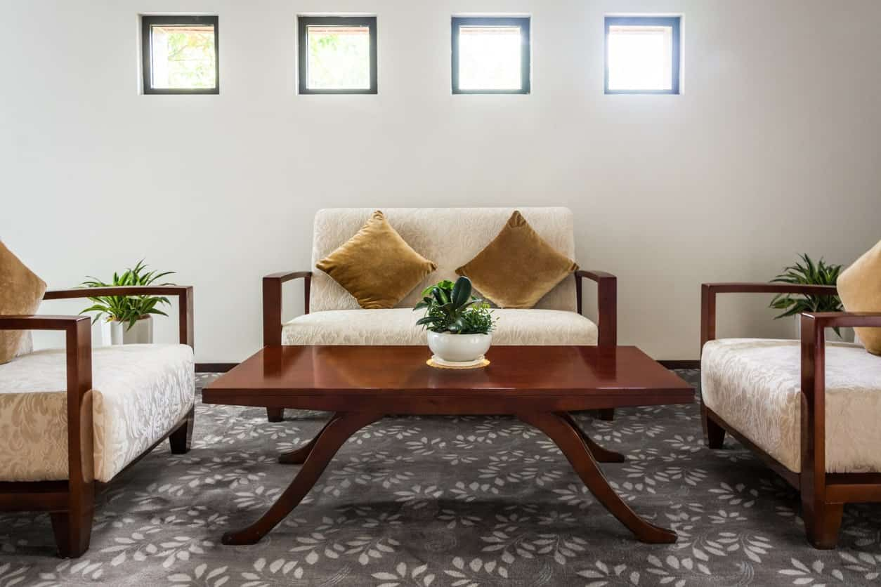 This simple living room is dominated by a background of dark gray carpeted flooring that has oriental floral designs pairing with the subtle patterns of the cushioned white armchairs and bench that matches the wooden coffee table.