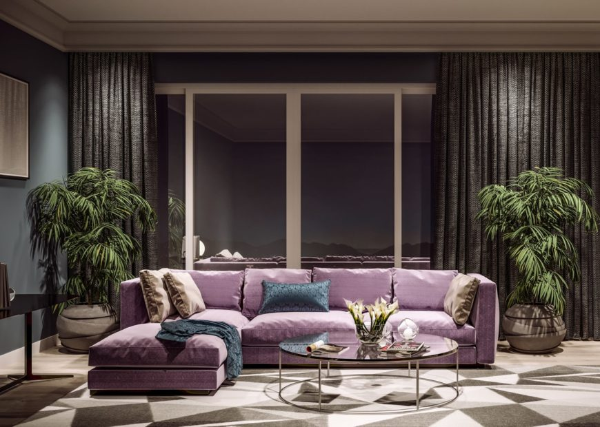 This luxurious living room is dominated by a large L-shaped sectional sofa that has a light purplish hue contrasting the modern circular glass-top coffee table over the geometric patterns of the area rug flanked by a couple of potted plants.
