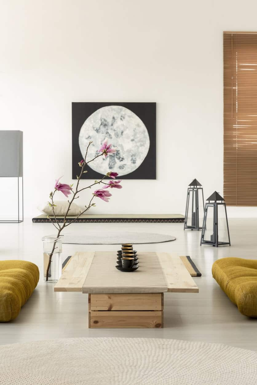 This simple Japanese-Style living room has a white flooring topped with a floor-height wooden table with a light gray table runner paired with a couple of yellowish cushions on the floor with a side of a branch with flowers in a flower vase.