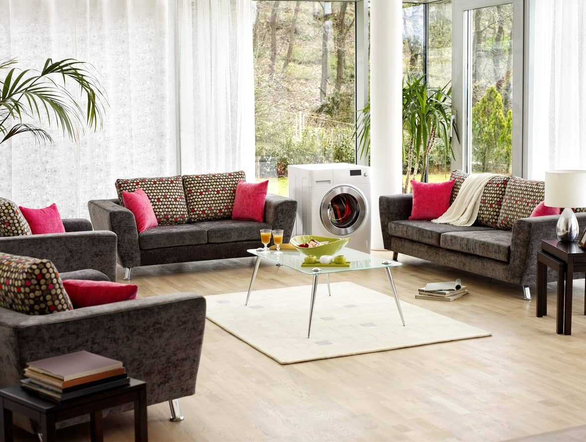 This bright and airy living room has a peculiarity that catches the attention which is the washing machine in between the two dark gray velvet sofas that matches the armchairs as well as the matching colorful pillows all surrounding the glass-top coffee table.