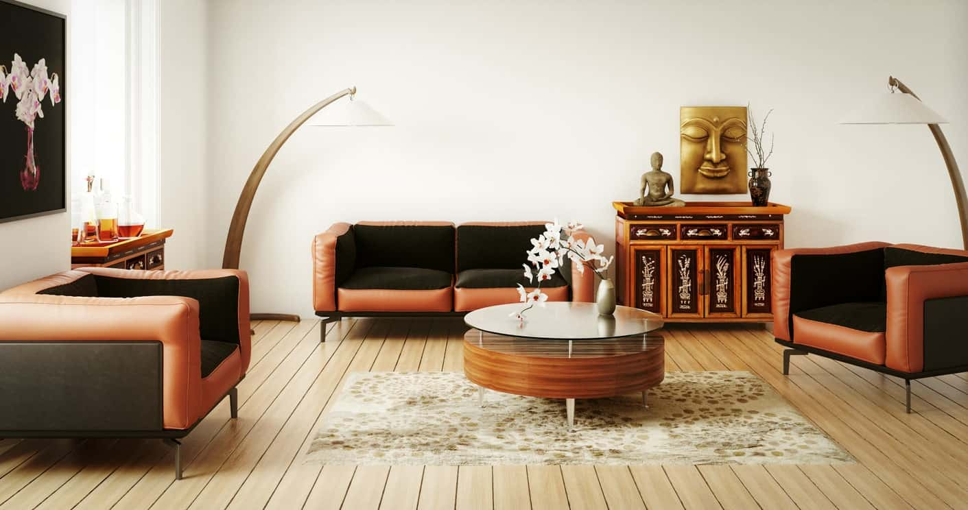 There is a Buddha artwork and statuette adorning the oriental dresser beside the orange and black cushioned sofa set that surround the circular glass-top coffee table over the patterned area rug of the light hardwood flooring.