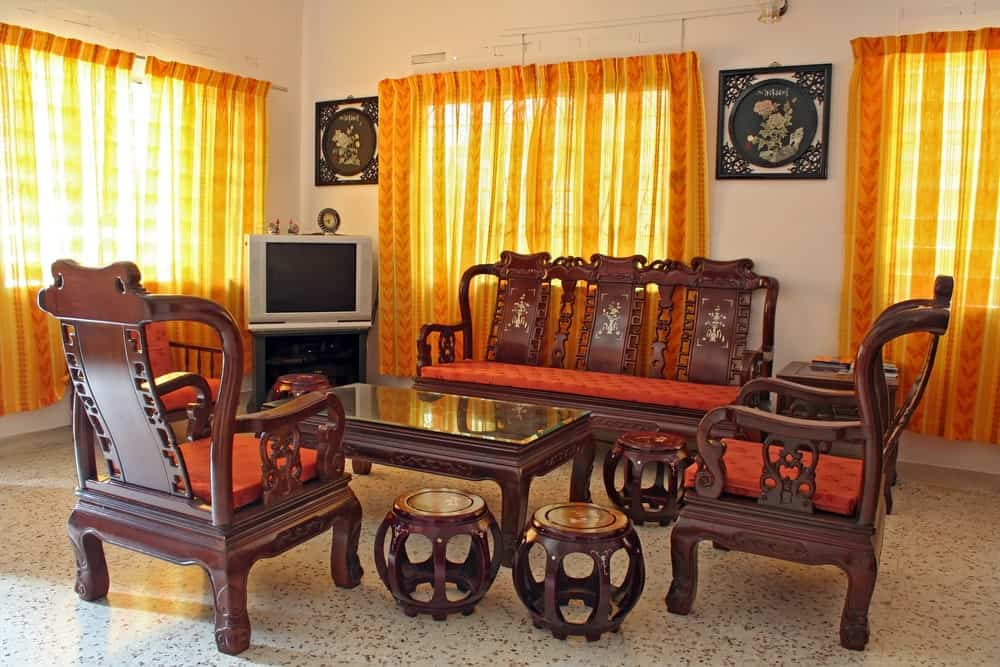 This is a simple and classic oriental-style living room that has wooden armchairs and bench with oriental carvings that match the small circular foot stools that contrast the white flooring reflecting the orange curtains of the windows.