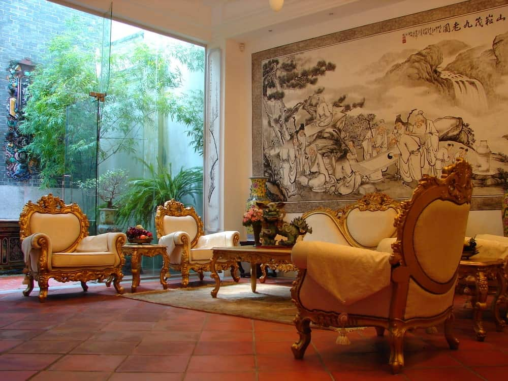 The white leather sofa and matching armchairs have a carved golden frame that has oriental designs that complement the large wall classic oriental mural. This is augmented by a glass wall that features a small garden outside.