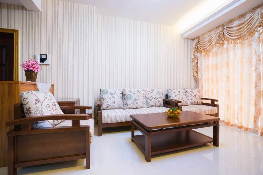The simple white ceiling and walls filled with a striped wallpaper matches with the cushions of the wooden bench and armchair facing the rectangular wooden coffee table that stands out against the white flooring that reflects the orange curtains of the window.