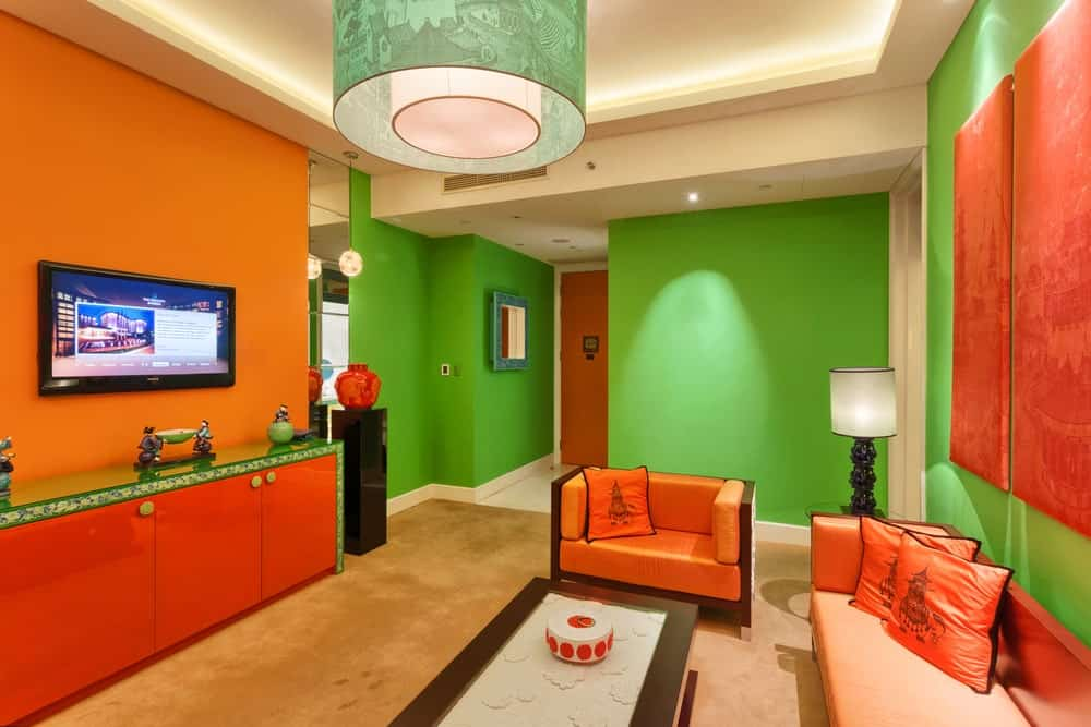 This delightful living room has oriental palettes of orange and green that is mediated by the beige carpeted flooring. The orange wall-mounted decors on the green wall have subtle oriental patterns that match with the prints of the orange throw pillows on the orange sofa set.