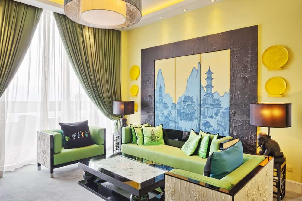 There is a nice oriental-style mural that accents the yellow wall behind the green cushioned bench that matches with the green armchairs and black rectangular coffee table that stands out against the white carpeted flooring and curtained windows.