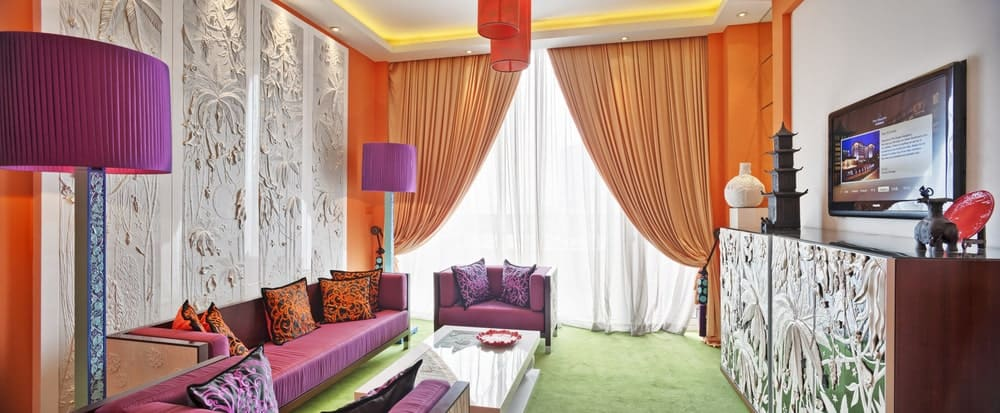 This cheerful living room has orange pendant lights that match with the curtains and walls. The purple standing lamps match the purple cushioned bench and armchairs that stand out against the green carpeted flooring and white textured mural behind the bench.