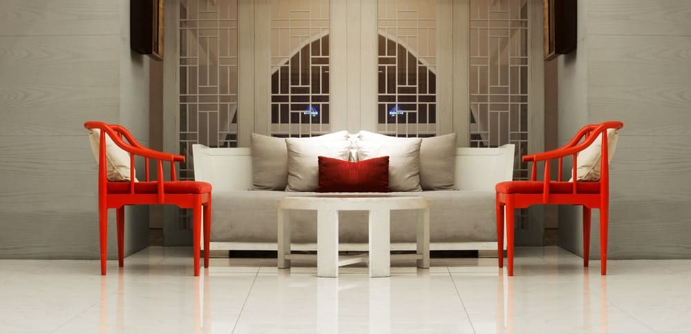 This is a simple living room with a sleek white flooring that blends with the white circular coffee table and white cushioned sofa contrasted by the two orange armchairs with orange cushions and white pillows.