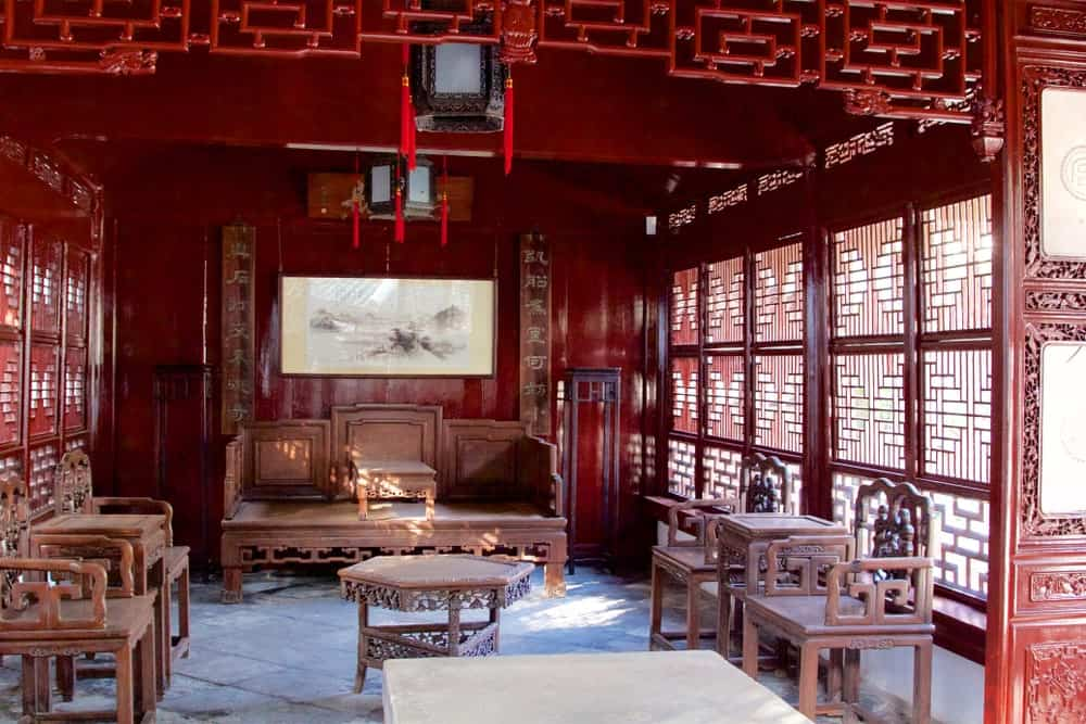 This is a traditional Chinese-Style living room that has oriental patterns on its windows that matches with the carvings of the armchairs and wooden bench surrounding the small center table with the same carvings. These are topped with Chinese lanterns on the red wooden ceiling.
