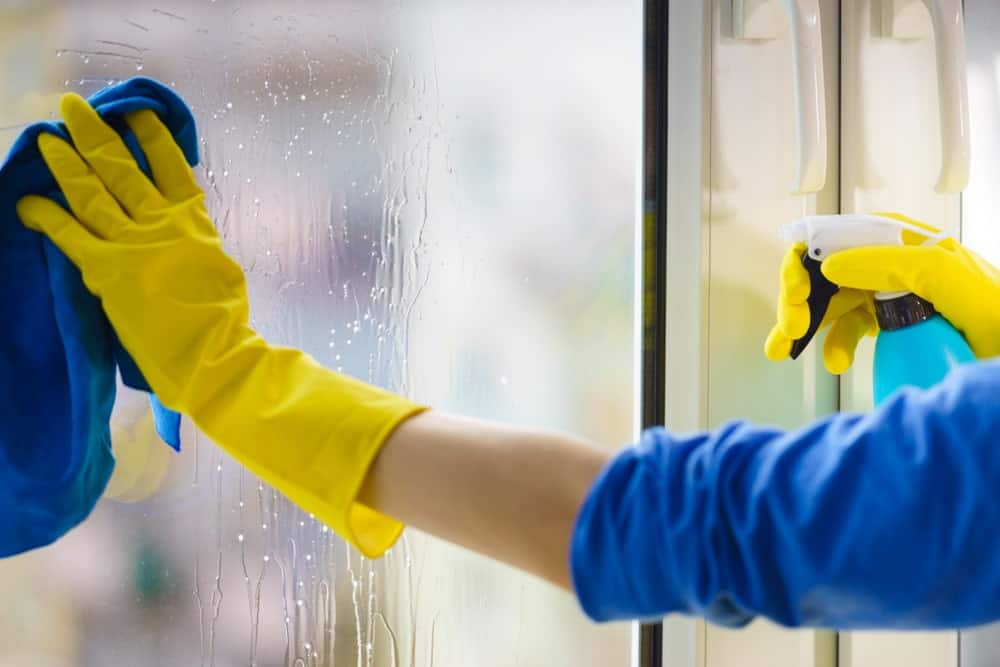 A girl cleaning window with glass cleaner
