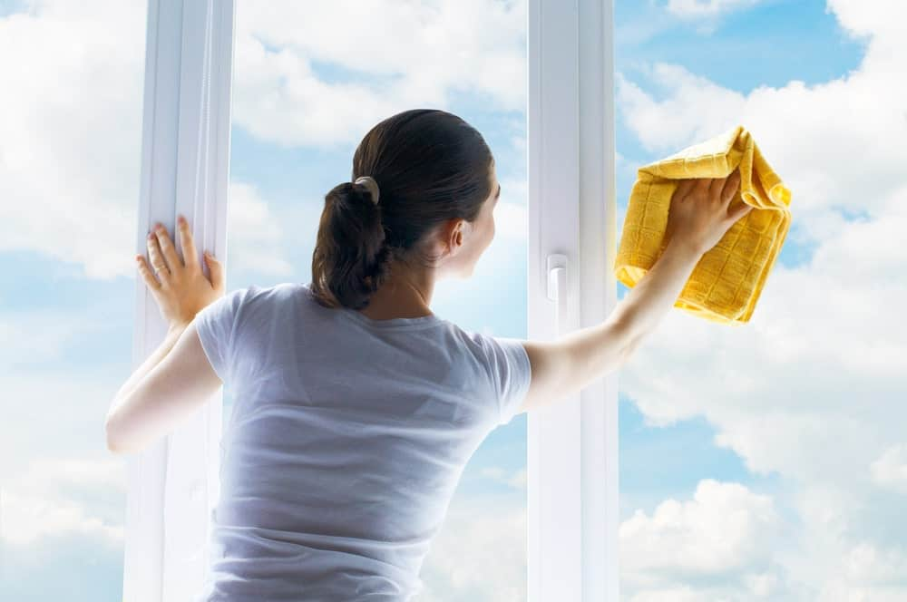 A woman cleaning glass window