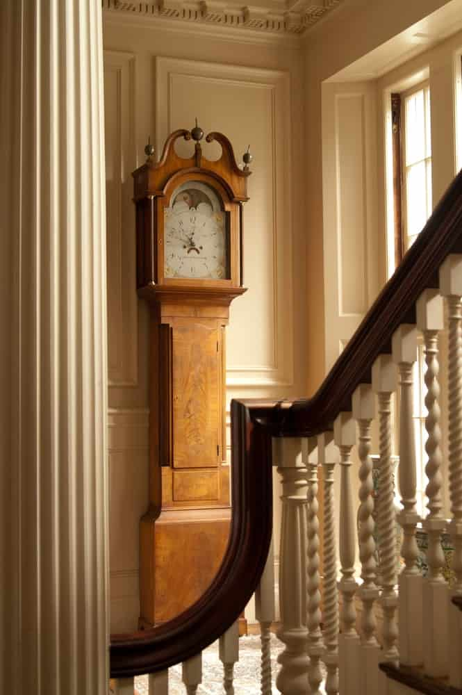 A slender longcase clock next to a staircase