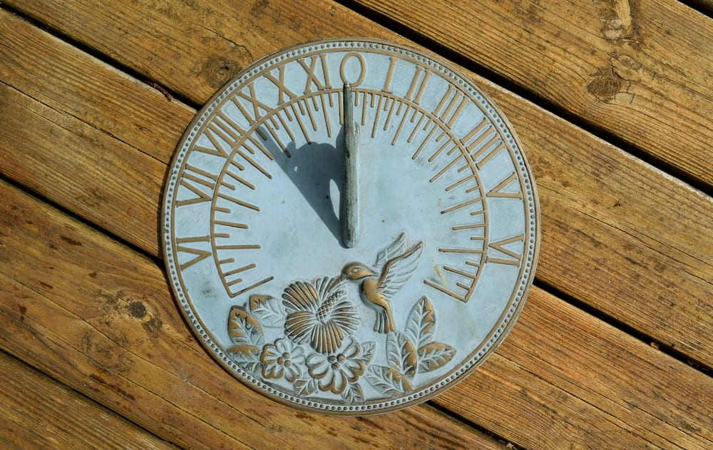 Sundial on a wooden background