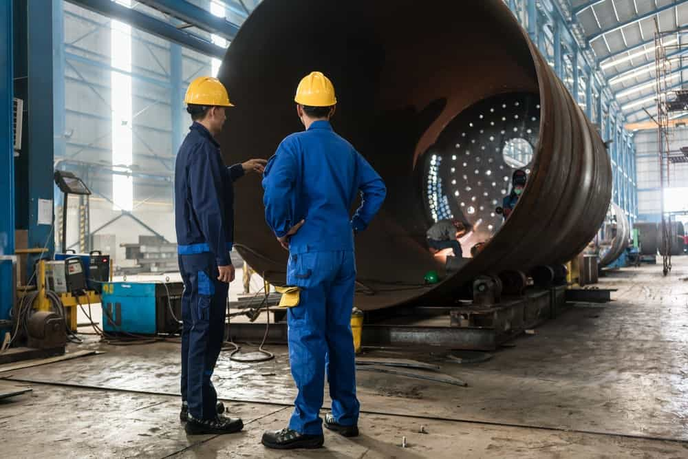 Two manufacturing welders supervising the manufacture of metallic cylinder