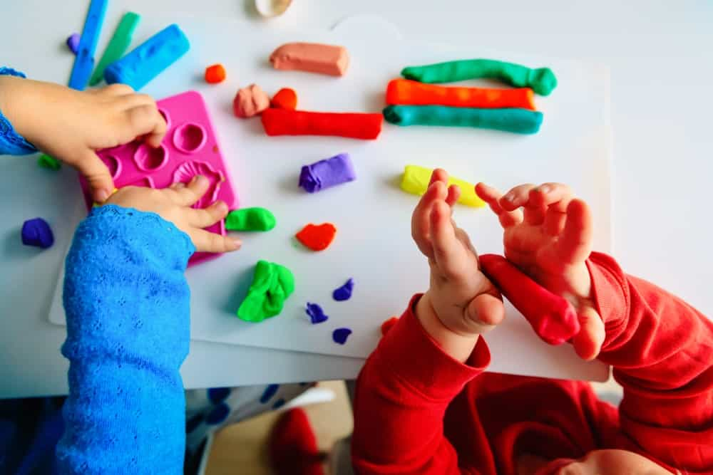 Children playing with colorful dough clay