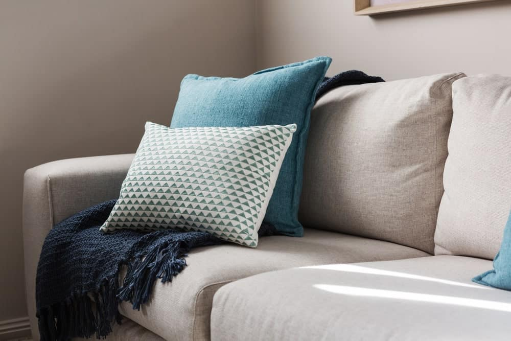 A sofa with cushions and throw