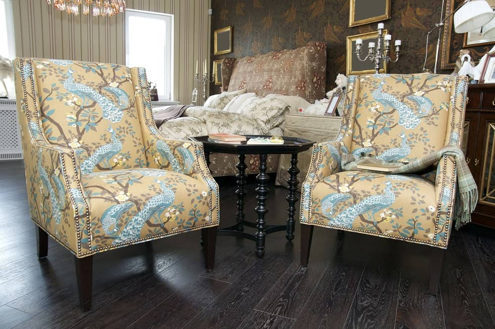 Twin upholstered chair printed with peacocks in a Traditional style primary bedroom.
