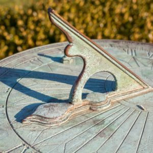 A sundial with a green patina