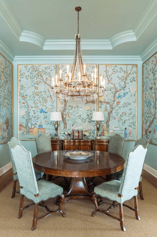 Charming dining room illuminated by a round candle chandelier that hung from the stylish tray ceiling. It has a wooden buffet table that complements the round dining table surrounded by blue high back chairs.
